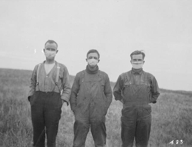 Albertan farmers wearing masks to protect themselves from the flu. ชาวแคนาดา จาก เอลเบอร์ตา สวมหน้ากากป้องกันตน จากไข้หวัดใหญ่สายพันธุ์ H1N1 เมื่อครั้งระบาดใหญ่ 1918 flu pandemic ในรัฐแอลเบอร์ตา